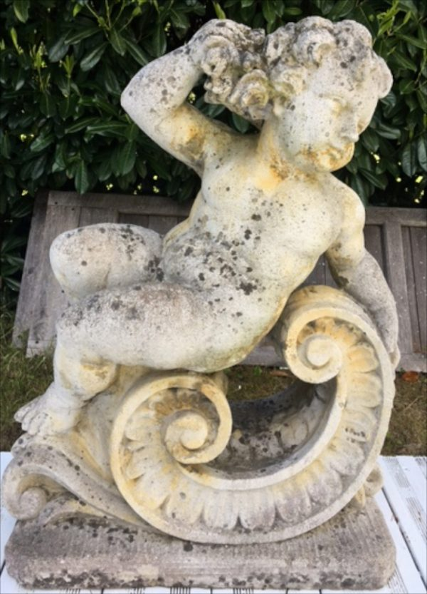 vintage french cherub statue in reclining position